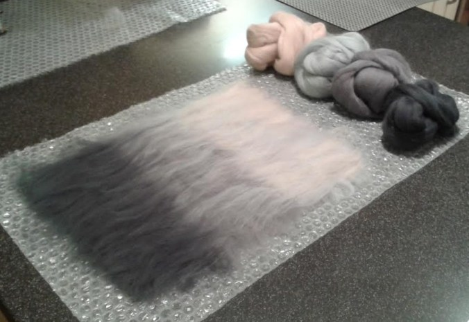 Fibres laid out ready for felting - three shades of grey and a flesh tone to add a little warmth.