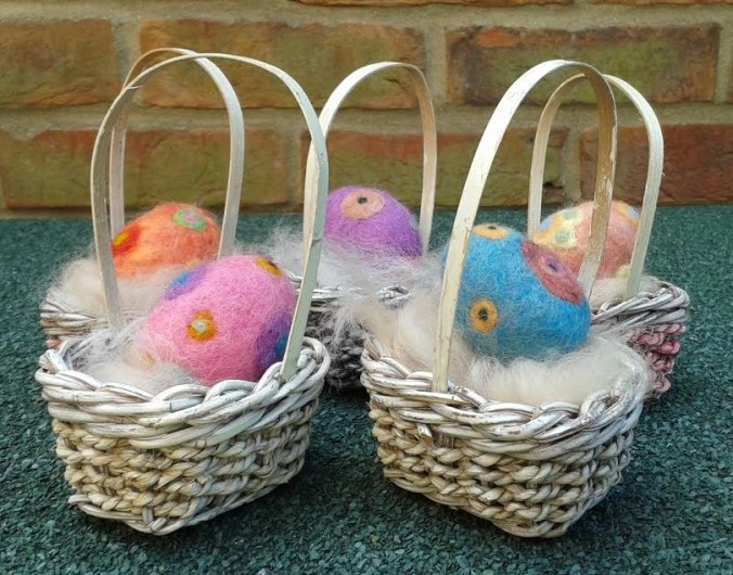 A collection of polystyrene eggs decorated with needle felting.