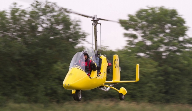 Yellow RotorSport Gyro flying low