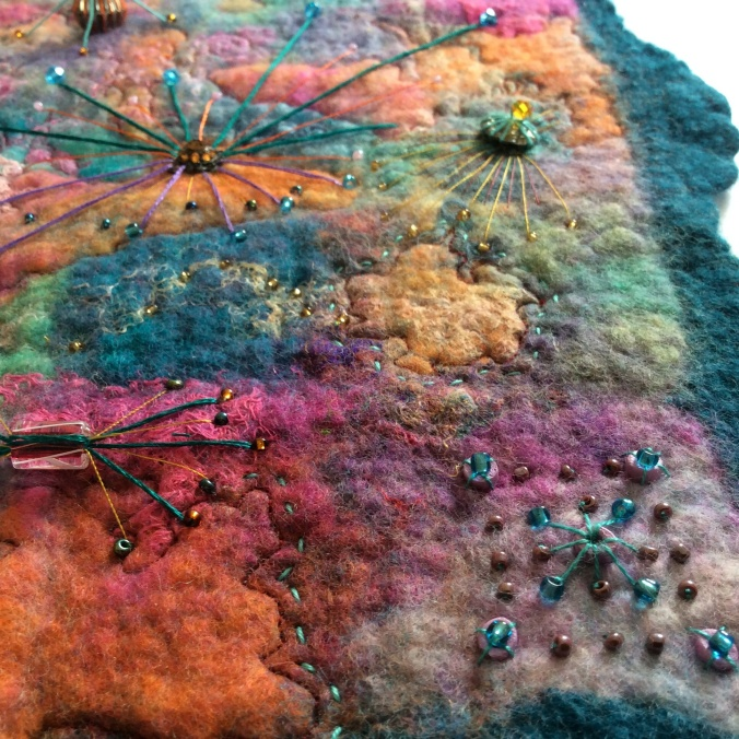 Close up detail showing beading and hand stitching on colourful wet felted picture.