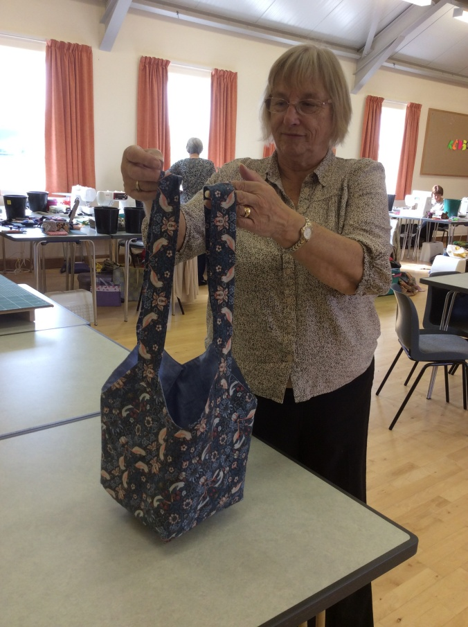 One of the ladies at The Sitting Ducks quilters group showing her handmade blue tote bag.