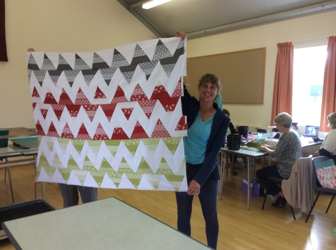 A bold patterned 'Zigzag, quilt in white, red, green and grey fabrics.