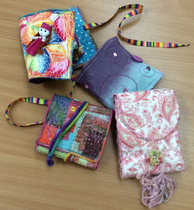 A variety of pocket books created using different fabrics.