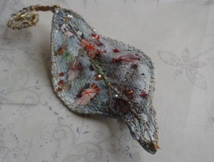 My blue/green handmade leaf stitched with metallic thread and embellished with tiny coloured beads.