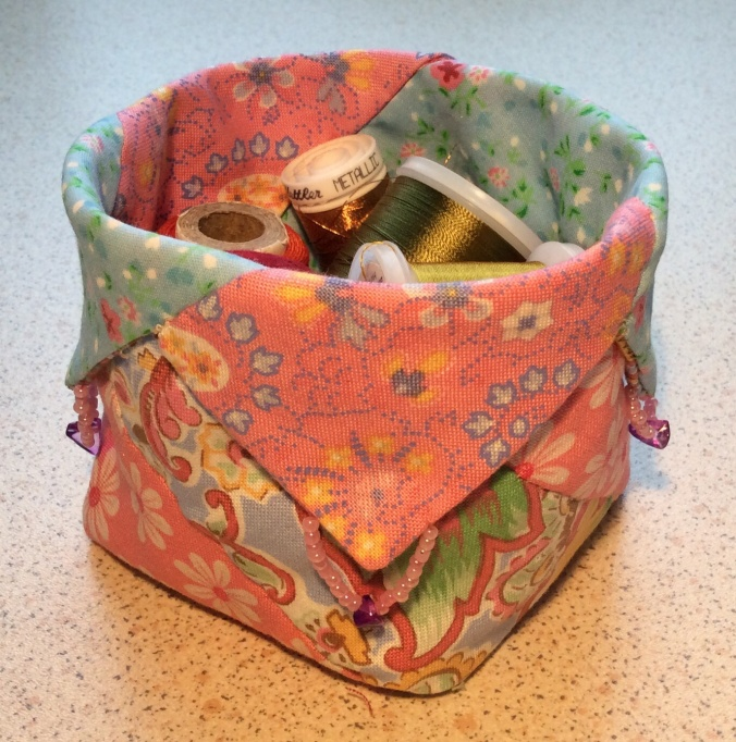 Small square shaped container made from four different patterned fabrics