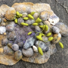 The image shows a small wall plaque created using Bergschaf fibres. The plaque is in the shape of a rock pool with seaweed.