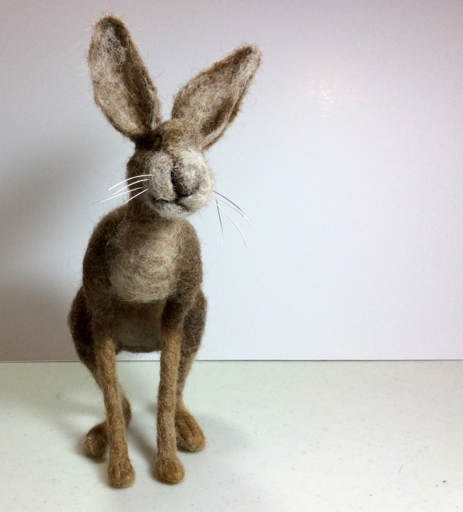 Needle felted brown hare looking towards the viewer