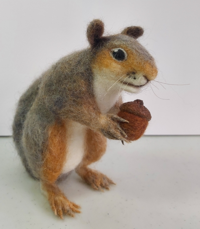 A needle felted grey squirrel holding an acorn